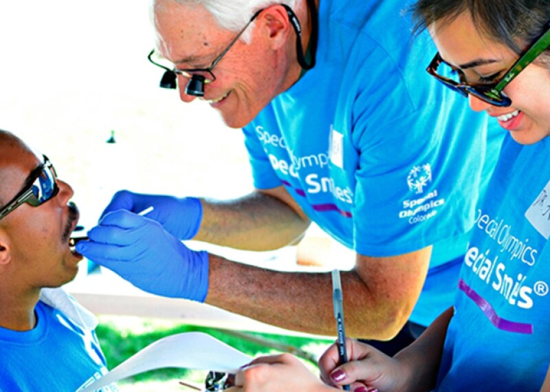Athlete receiving a dental examination and an assistant takes notes.