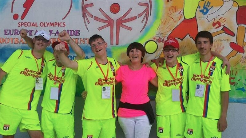 Tali (in pink and white) with team France footballers (in fluorescent yellow) outside in front of a mural.