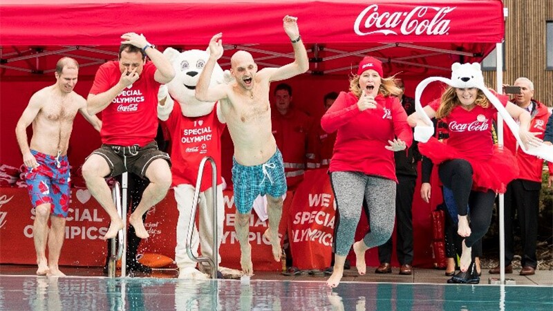 Four people jumping in the water at the Polar Plunge. The Coca Cola booth is in the background.