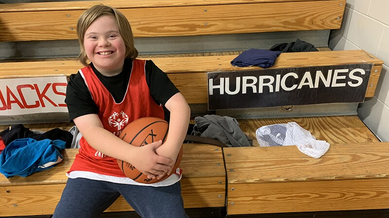 "Boy smiling sitting on bleachers holding a basketball wearing a red Special Olympics tank top with a team sign, ""Hurricanes"" in the background."