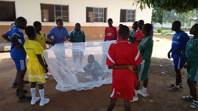 Students and athletes gather around a student under mosquito net and all are listening to a speaker.