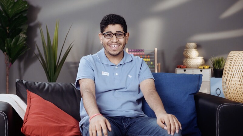 Ahmad sitting on a couch in a blue polo shirt smiling for the photo.