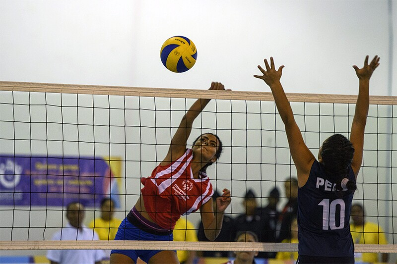 Two young women playing volleyball; one is jumping to spike the ball and the other is jumping to defend.