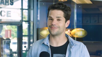 Max Carver smiling in front of the Warren High School trophy cabinet