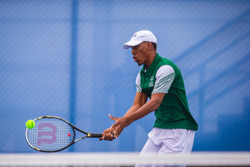 A Special Olympics athlete hits the tennis ball with his racket.