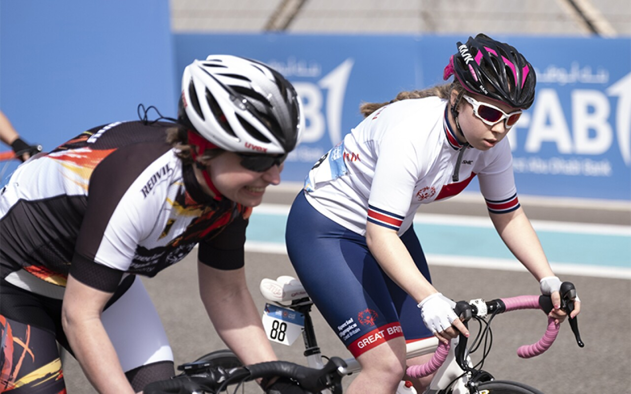 Kiera riding her bike next to another athlete. Both have safety helmets on.