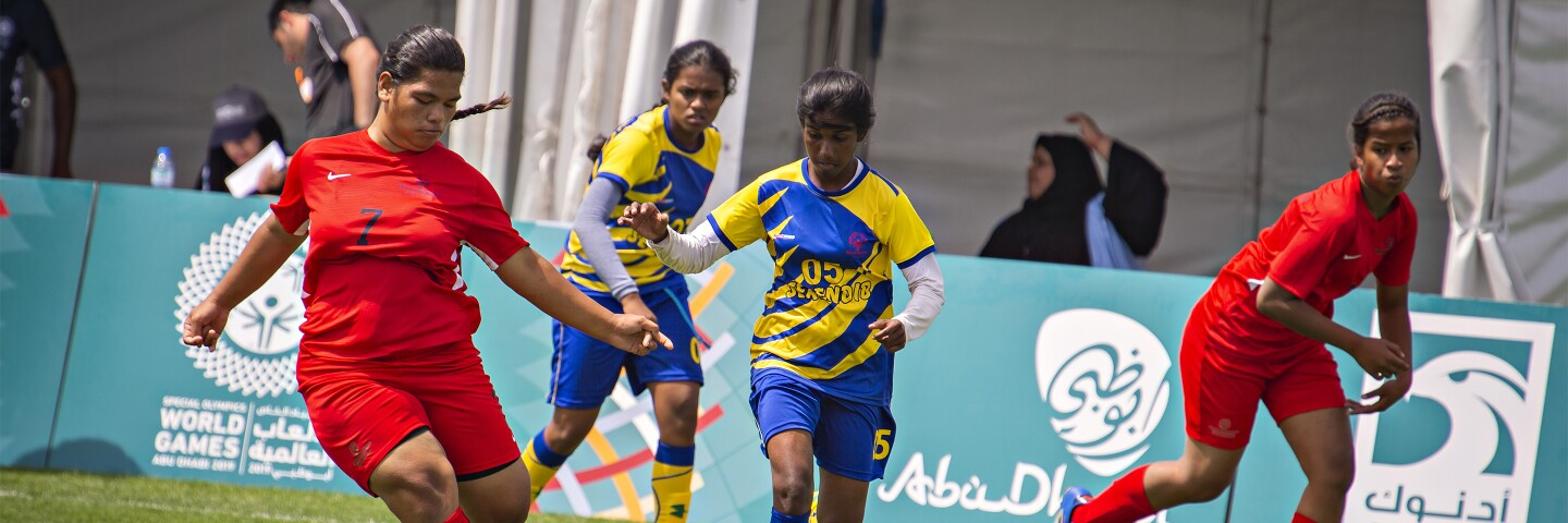 Four young women on the field playing football, two from each team with spectators in the background.