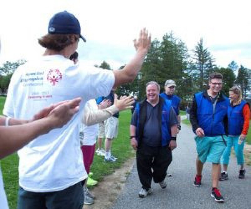Unified Partner with his back to the photo is greeting a small group of athletes and Unified Partners from Special Olympics walking toward him at a Unified Fitness Club.