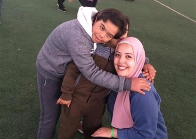 A young adult woman and two elementary school aged boys, all with big smiles, hug each other on an indoor sports field.