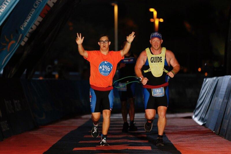 Chris Nikic and Dan Grieb cross the finish line at IRONMAN Florida in Panama City.