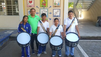 Professor Pedro Balbuena stands with four teenage Unified Athletes and partners holding drums at a school in Guerrero, Mexico.