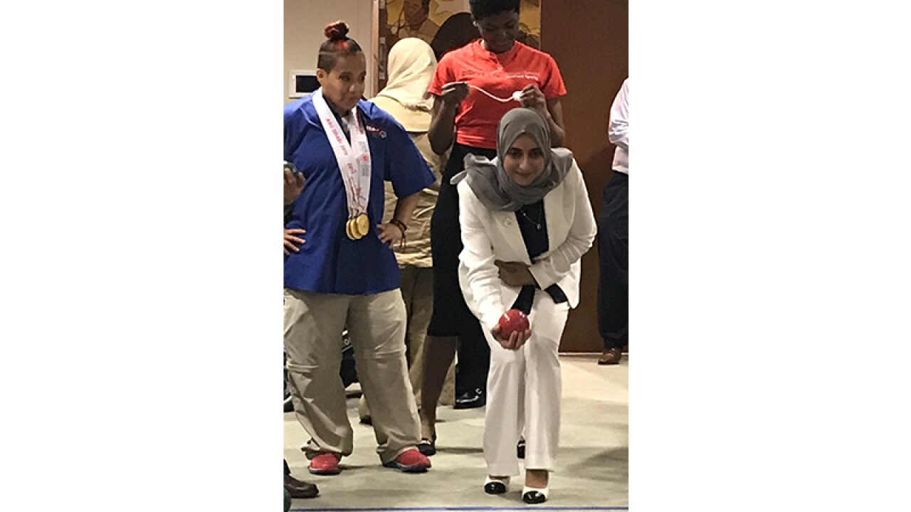 A young woman in a head scarf is lining up the Bocce ball to make a toss. An athlete watches her.