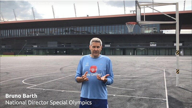 Bruno Barth on the basketball court with a Play Unified long sleep blue shirt on talking to the camera.