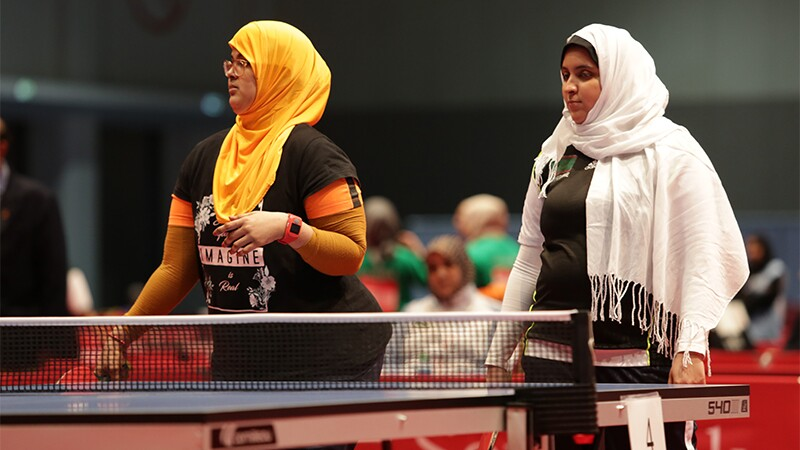 Khadija (left) and Mariem (right) standing at the table tennis table awaiting the competition to start.