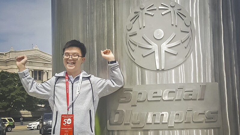 Johannes standing next to a metal sign of the Special Olympics with his arms up in celebration and smiling.