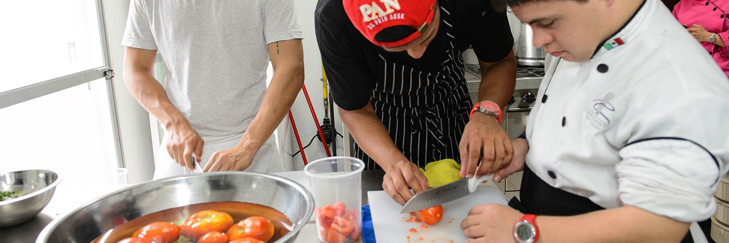 a chef showing an athlete how to cut a tomato.