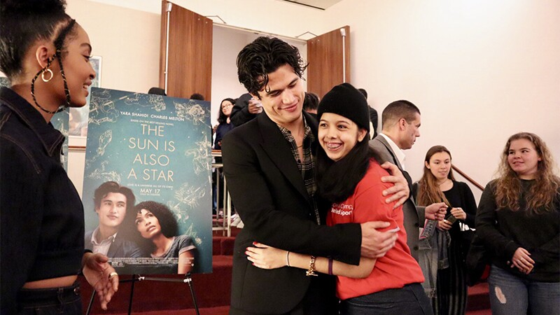 Actor Charles Melton gives female Special Olympics athlete a hug.