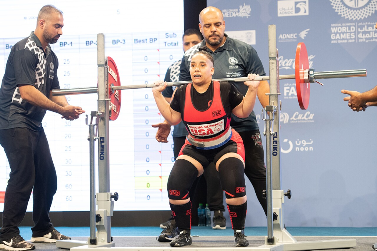 Angel, a power lifter lifting weights over her shoulders. a spotter is on either side of her and two are behind her.