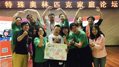 Attendees of the Special Olympics Family Forum in Xi'An, China are in a group, six males and females in the front row and six in the back row, the back row is making a heart shape with the their hands and arms above their head with the person next to them. A young man in the front is holding a poster with notes and a drawing of two hands inside a heart.