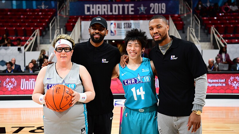 Coaches Kyrie Irving and Damian Lillard stand with players Leanne Woolfe, Special Olympics Great Britain and Mikami Hayato, Special Olympics Japan on the basketball court.