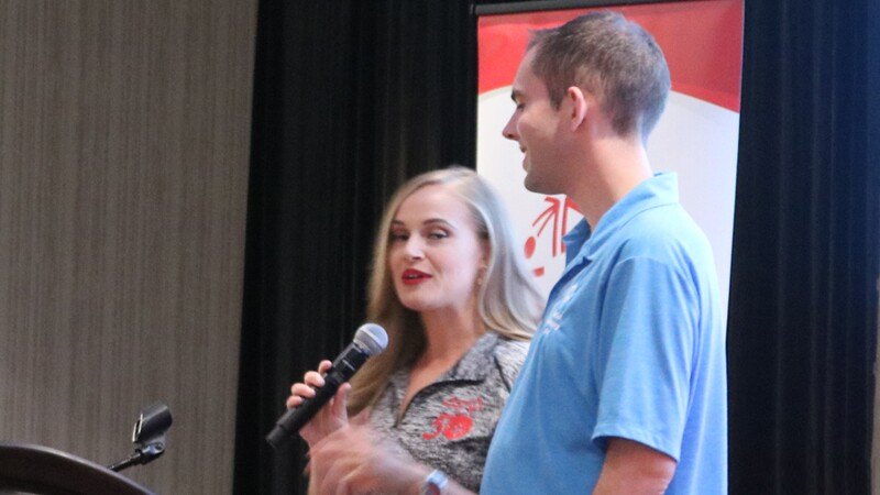 Tyler Leech standing next to a woman speaking into a microphone; both are behind a podium.