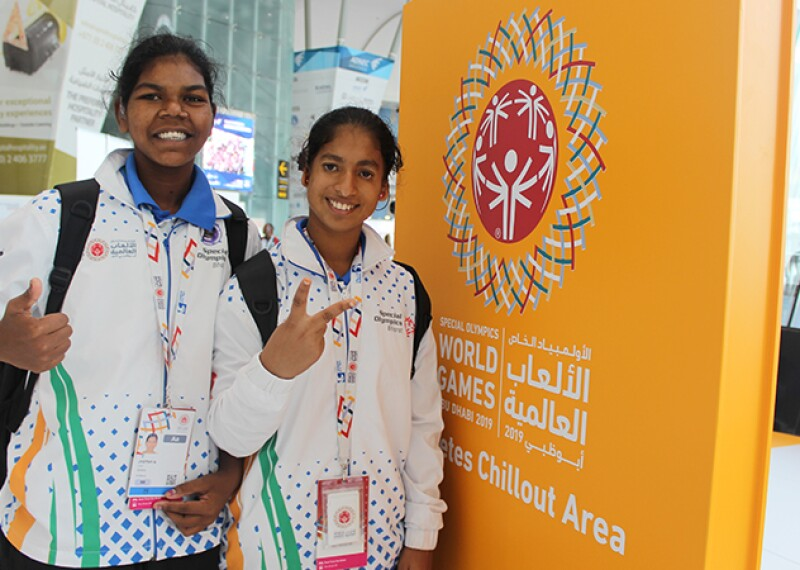 Two young women standing in front of an Athletes Chillout Area sign at the 2019 World Games giving a peace sign and a thumbs up.