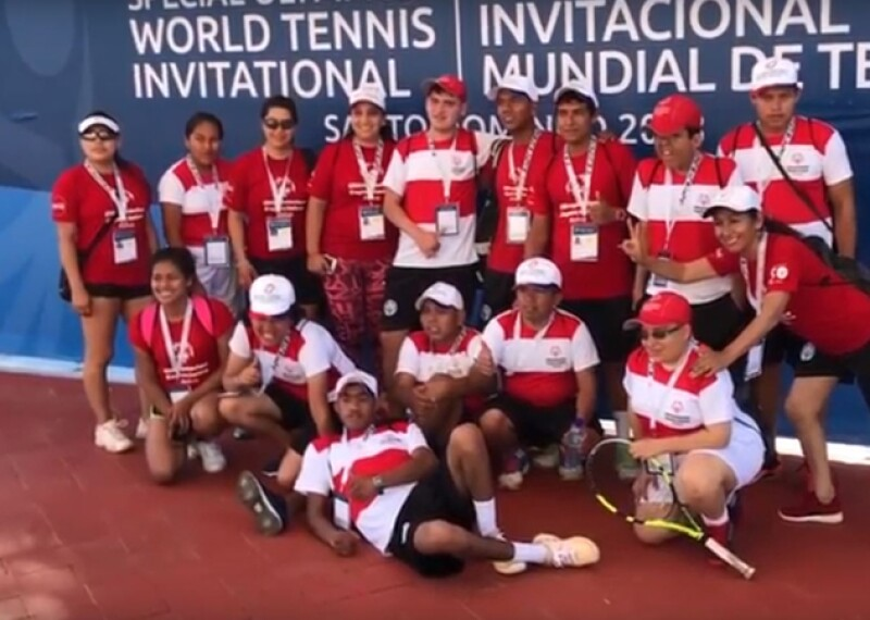 Athletes, representatives, and friends gather together in a group in front of the World Tennis Invitational sign for a group photo. Every is wearing a white and red or red polo shirt.