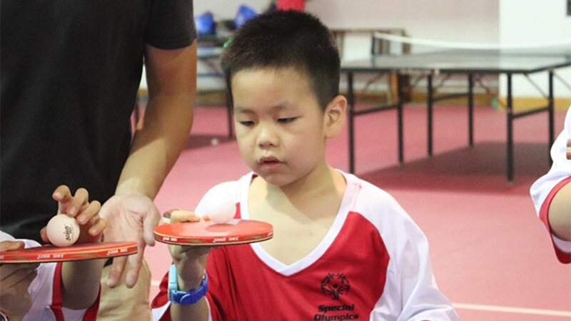 A young athlete is playing table tennis during 2018 Special Olympics East Asia Unified Camp. He is wearing a red and white Special Olympics jersey and a blue watch. He has a ping pong paddle in his right hand and balancing a ball on top which he is intently staring and consecrating on.