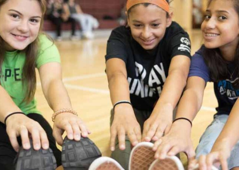 Three young girls sitting on the gym floor stretching and touching their toes.