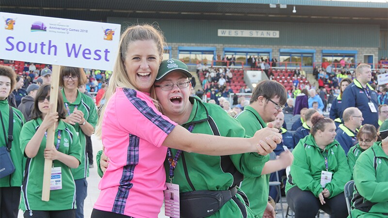 An athlete and an Special Olympics representative are dancing with one another and smiling for the photo.