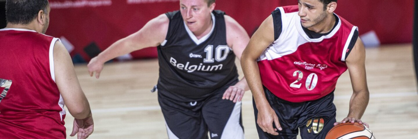 Three basketball players on the court. One is dribbling the ball.
