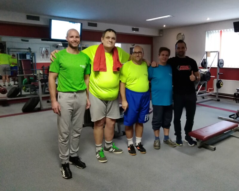 Special Olympics coaches and athletes stand in a gym in work-out gear.