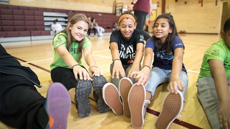 Three female students sitting on the gym floor doing a toe-touch stretch.