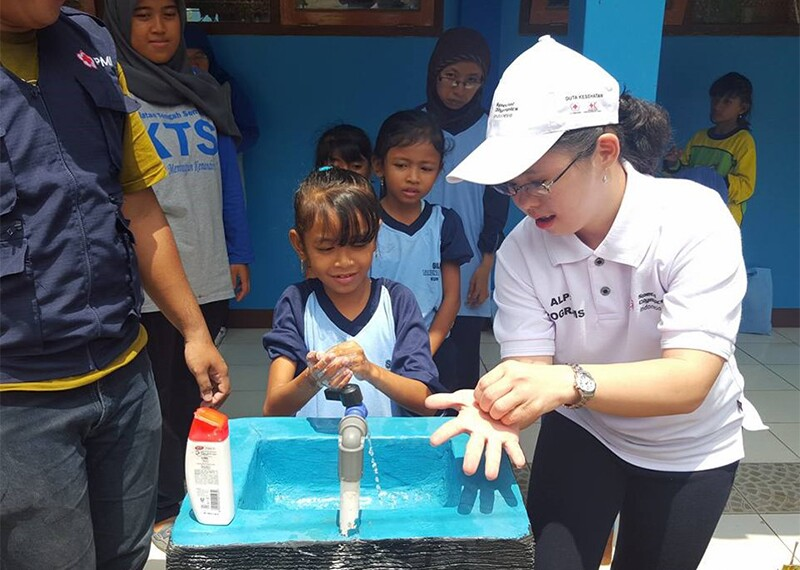 Athlete, Stephanie Handojo, demonstrating proper hand washing techniques to young children.