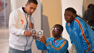 Young athlete is given an eye exam by a volunteer while another athlete watches.