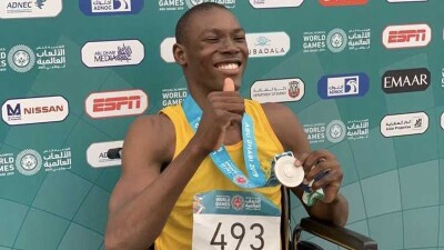 young man in a yellow tank top and black shorts sitting in a wheel chair showing off the medal around his neck.