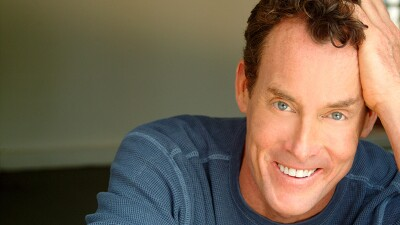 John C. McGinley's professional head shot. He's resting his hand on his head and leaning into the photo on his elbows. He has on a blue thermal shirt.