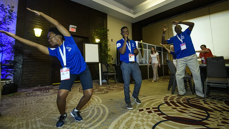 International Global Messenger, Brightfield Shadi leads a dance party to loosen up the Global Athletes Congress attendees. Two additional athletes accompany him, an older male and a female.