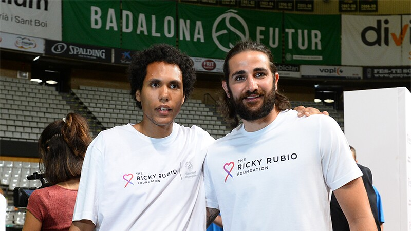 Special Olympics Spain athlete on the the left is with NBA star and Special Olympics Global Ambassador Ricky Rubio on the right. Standing with one arm around each other both have on t-shirts that read: The Ricky Rubio foundation.