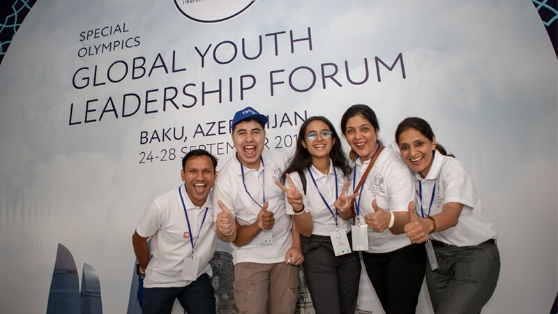 Global Youth Leadership Forum attendees posing in front of signage at the event in Baku. There are two men on the left and three women on the right. All wearing white shirts with excited expressions on their faces giving a thumbs up or the peace sign.