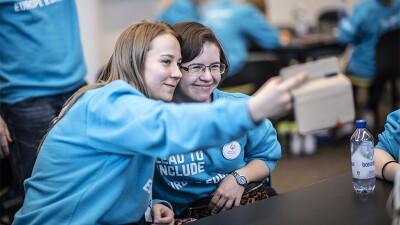 Two girls sitting side by side taking a selfie.