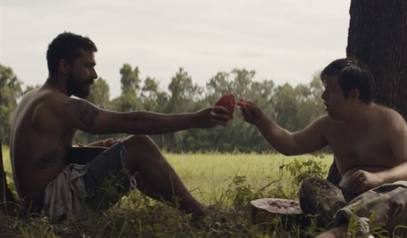 Move still from Peanut Butter Falcon, two men sharing food sitting outside under a tree