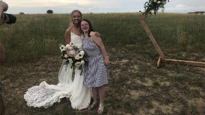 Hanna standing next to a bride as the bride holds a bouquet and has her arm around Hanna's shoulder.