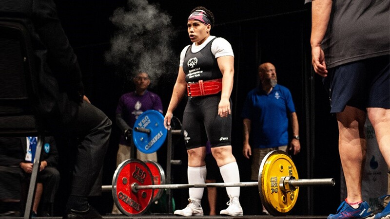 Angel preparing to dead lift; she's standing on stage.