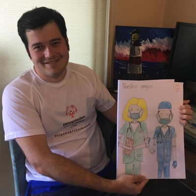 Isaac González posa con una de sus obras, un dibujo de doctores robots.