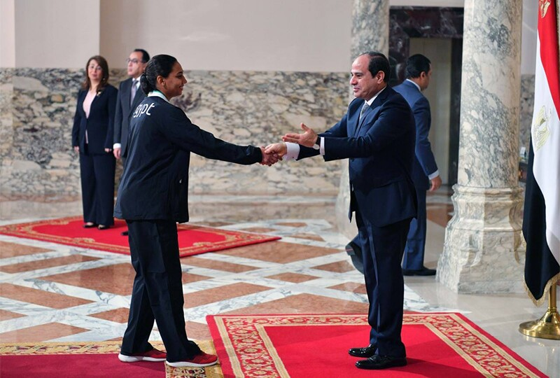 The Egyptian president shakes hands with a female athlete to recognize her achievement.