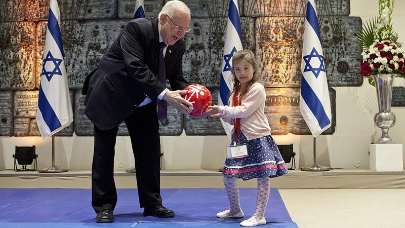 Shay Dagan Plessman presenting Israeli President Reuven Rivlin with a Special Olympics football.