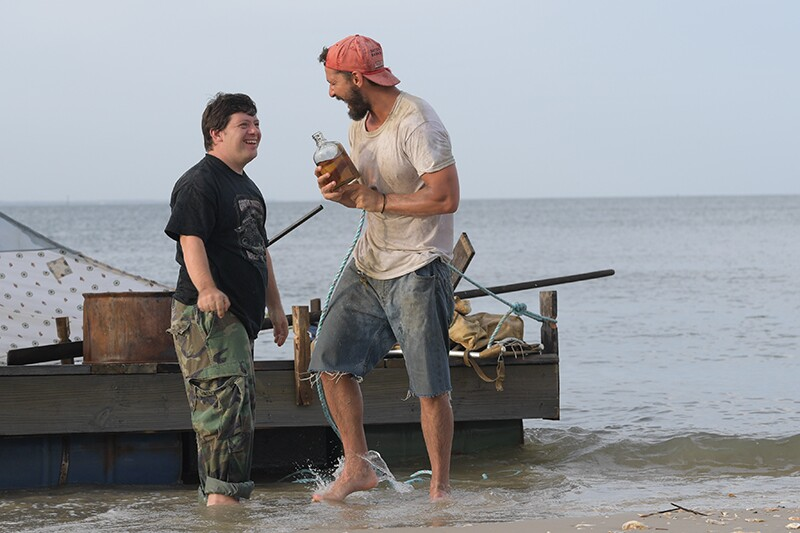 Zack Gottsagen and Shia LaBeouf laugh in front of a raft while filming The Peanut Butter Falcon.