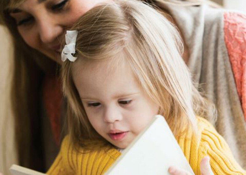 Young girl reads while mother figure watches from behind her.