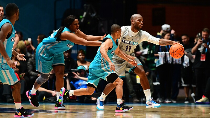 Taj McWilliams tries to catch Didier Drogba (dribbling the ball) on the court.